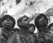 """SIX DAY WAR. ISRAELI PARATROOPERS STAND IN FRONT  OF THE WESTERN WALL IN JERUSALEM. ANY COMMERCIAL USE OF     THIS PHOTO REQUIRES EXPLICIT PRIOR GPO PERMISSION.  öðçðéí çééìé öä""""ì ðøâùéí, ìéã äëåúì äîòøáé áéøåùìéí, ìàçø ùéçøåø äòéø            äòúé÷ä áîìçîú ùùú äéîéí.                                                         îéîéï ìùîàì, çééí ëäï, éöç÷ éôòú åöéåï ÷øñðèé.                                   äùéîåù áúîåðä æå ìôøñåîú îñçøéú îåúðä áàéùåø îéåçã åîôåøù ùì ìùëú äòéúåðåú       äîîùìúéú."""