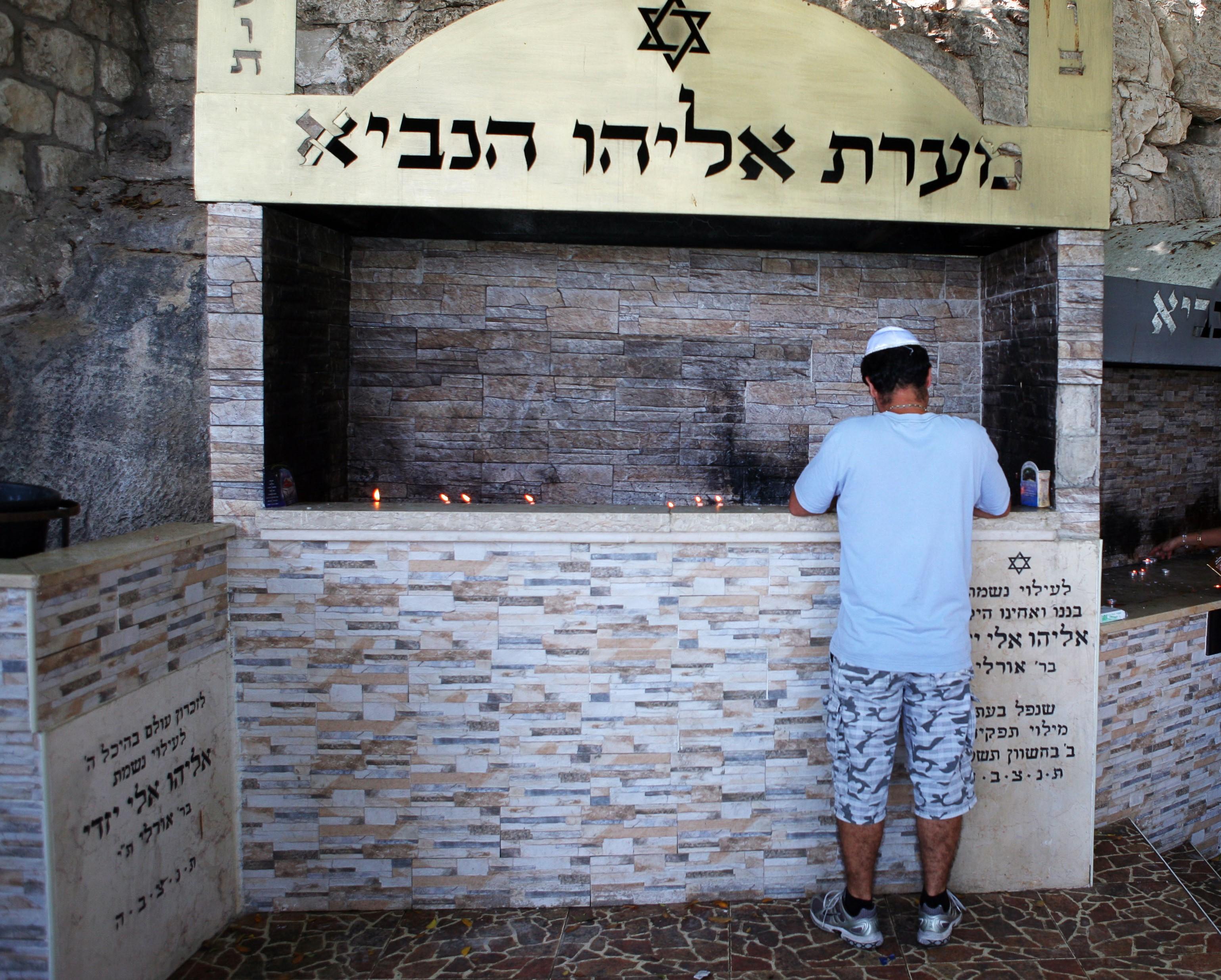 Ultra orthodox pray and light candles in Elijah's (Eliyahu Ha-Navi) cave